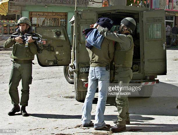 An Israeli borderguard blindfold a Palestinian detained in the center of the West Bank city of Hebron 07 December 2003 Israeli Prime Minister Ariel...