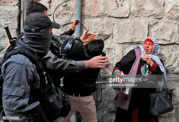 TOPSHOT An Israeli borderguard scuffles with a Palestinian man in the Old City of Jerusalem on December 22 as protests continue in the region amid...