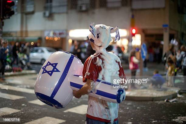 An Israeli boy is covered with foam as Israelis celebrate the Jewish state's 65th Independence Day on April 15 2013 in Tel Aviv Israel