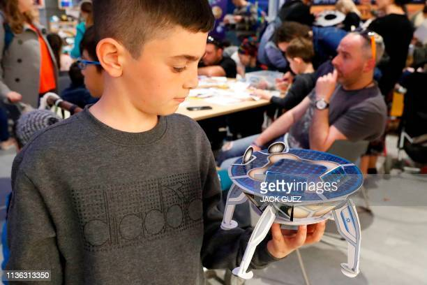 An Israeli boy plays with a model of Israeli spacecraft Beresheet's at the Planetaya Planetarium in the Israeli city of Netanya on April 11 2019...