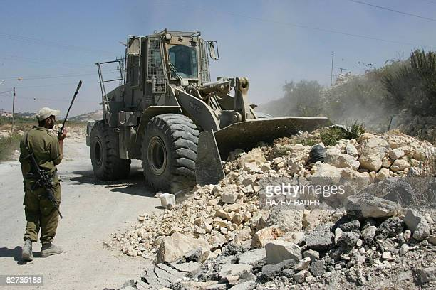 An Israeli bulldozer clears a road as Israel prepares to reopen the main entrance leading to the occupied West Bank city of Hebron which was closed...