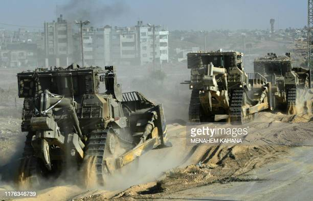 An Israeli bulldozer convoy move into the outskirts of the southern Gaza Strip town of Rafah 20 May 2004, on the third day of the massive Israeli...