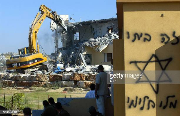 An Israeli bulldozer demolishes a house in the southern Gaza Strip Settlement of Dugit 21 August 2005Israel's pullout from the Gaza Strip entered a...