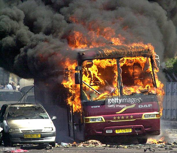 An Israeli bus and cars burn at the Beit Lid junction September 9 2001 in central Israel after a Palestinian bomber blew his explosivespacked car up...