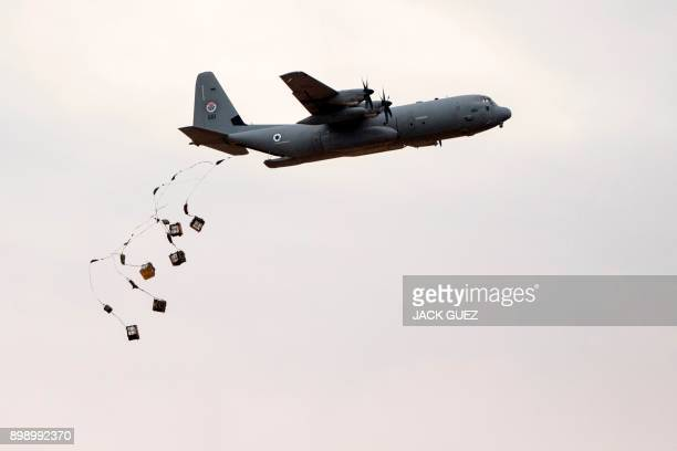 An Israeli C130 Hercules drops parcels during an air show at the graduation ceremony of Israeli air force pilots at the Hatzerim Israeli Air Force...