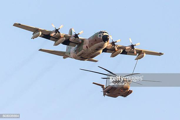 An Israeli C130 Hercules plane refuels a Sikorsky CH53K helicopter as they take part in an air show for a graduation ceremony at the Hatzerim base in...