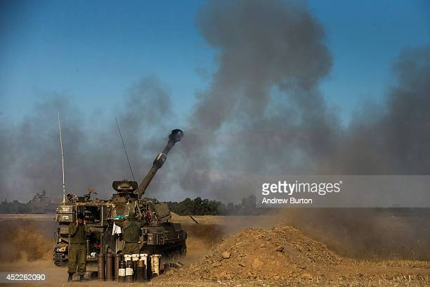 An Israeli cannon fires artillery shells into Gaza on July 17 2014 near Sderot Israel As the Israeli operation 'Protective Edge' enters its tenth day...