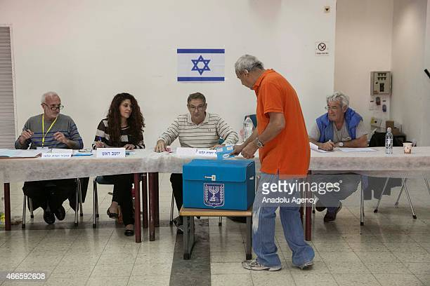 An Israeli citizen casts his vote at a polling station during legislative election in Tel Mond Israel on March 17 2015 Voting begin in Israels...