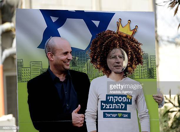 An Israeli citizen poses with the poster of Naftali Bennett during legislative election in Jerusalem Israel on March 17 2015 Voting begin in Israels...