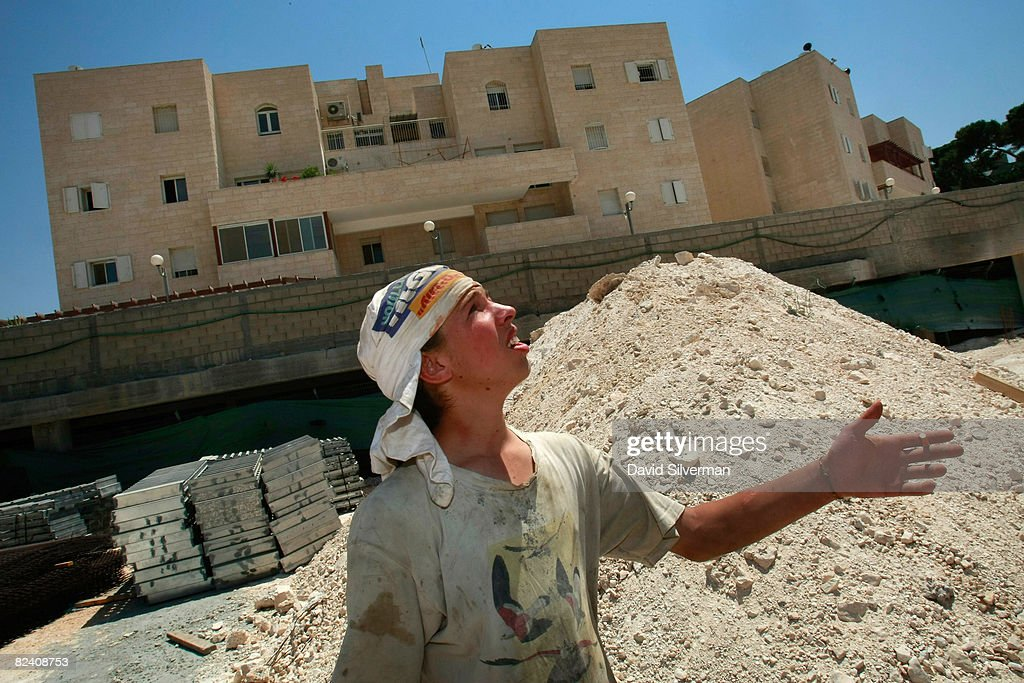 An Israeli construction worker keeps an eye on a crane working above the building site for an extention to the Maale Zeitim (Olive Heights) religious settlement (rear) on the Mount of Olives August 18, 2008 in East Jerusalem. The settlement, an apartment complex which houses dozens of families, is being built with funding from the Florida-based bingo and gambling magnate Irving Moskowitz by the Ateret Cohanim organization, which is dedicated to expanding Jewish settlement in East Jerusalem, the half of the city that Israel captured from Jordan in the 1967 Six Day War.