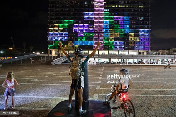 An Israeli cyclist plays against foreign visitors in a giant Tetris tournament illuminating the windows of the facade of the Tel AvivYafo...