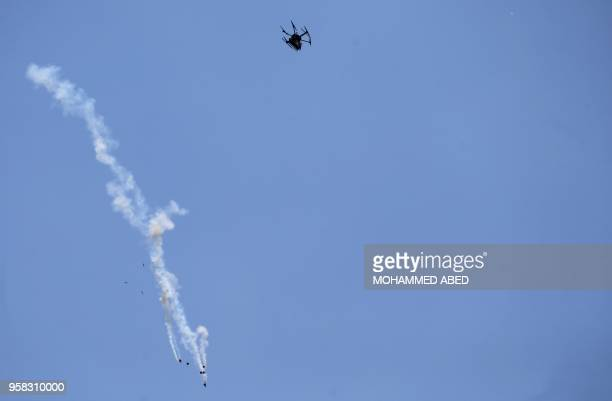 TOPSHOT An Israeli drone drops tear gas canisters on Palestinian protesters during clashes with Israeli forces near the border between Israel and the...