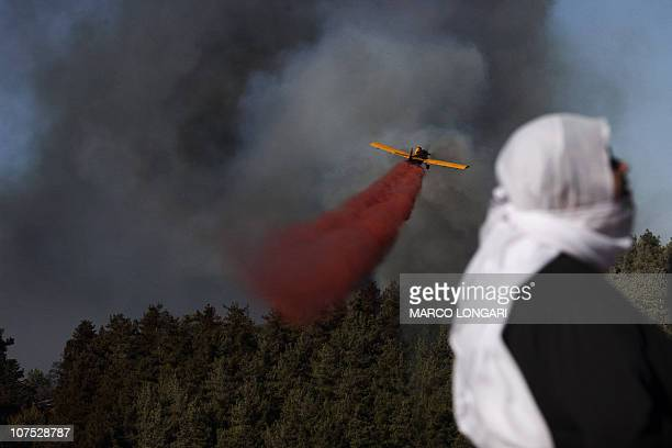 An Israeli Druze woman looks on as a plane sprays the retardant chemical used to quell the latest front of the raging flames near the village of...