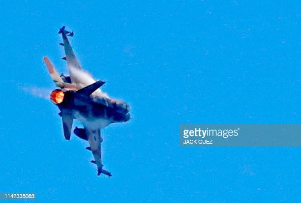 An Israeli F16 fighter jet performs during an air show over the beach in the Mediterranean coastal city of Tel Aviv on May 9 2019 as Israel marks...