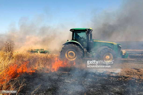 An Israeli farmer uses a tractor in an attempt to extinguish a fire in a wheat field near the Kibbutz Nahal Oz along the border with the Gaza Strip...