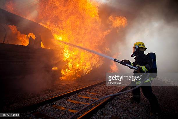 An Israeli fire fighter tackles a blaze after a train caught fire on December 28 2010 in Bnei Zion Israel The cause for the fire has yet to be...