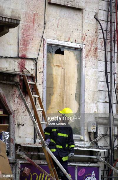 An Israeli firefighter clears debris from the scene of a suicide bombing March 21 2002 in a central Jerusalem shopping district The militant...