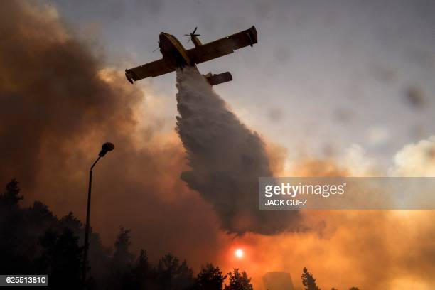 An Israeli firefighter plane helps extinguish a fire in the northern Israeli port city of Haifa on November 24 2016 Hundreds of Israelis fled their...