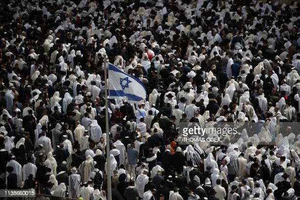 An Israeli flag flies among Jewish priests wearing Talit as they take part in the Cohanim prayer during the Passover holiday at the Western Wall in...