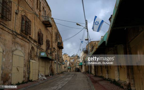 An Israeli flag flutters above the deserted Shuhada Street in the divided town of Hebron, in the Israeli occupied West Bank, on January 13, 2020. -...