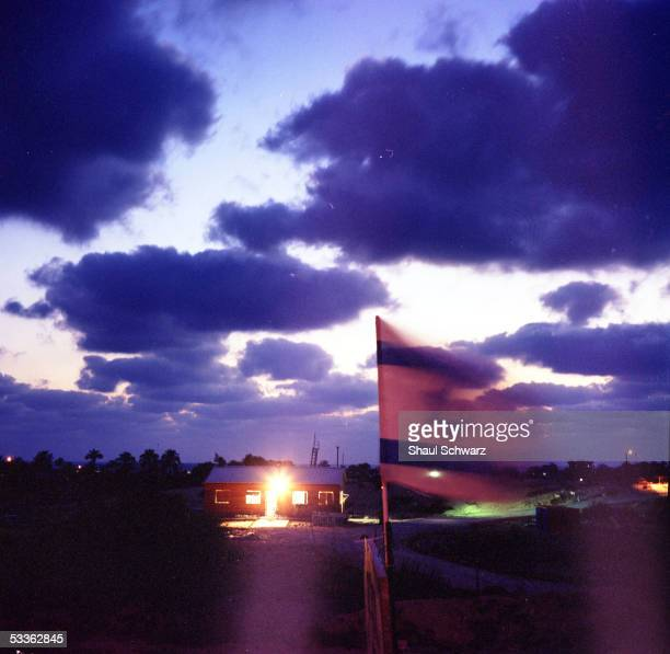 An Israeli flag flutters in the wind as a newly built settler outpost named Tiferet Yisrael is seen in the distance near the settlement of Neve...