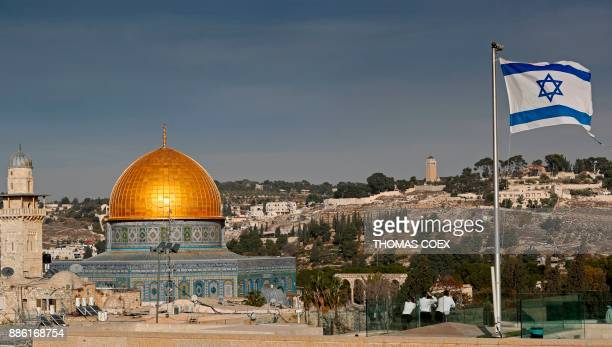 An Israeli flag flutters on the roof of a buiding of the Jewish Quarter in the Old City of Jerusalem opposite the Dome of the Rock in the AlAqsa...