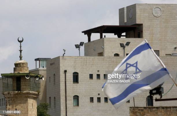 An Israeli flag is pictured near the minaret of a mosque at an Israeli settlement in the the old city of the West Bank town of Hebron on June 14 2019