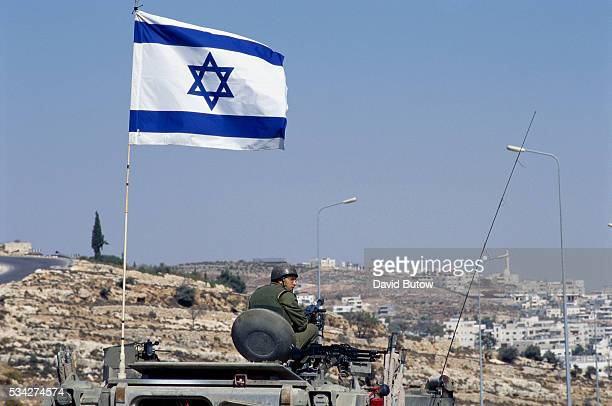 An Israeli flag is raised over a tank The soldiers are standing guard at a checkpoint in Jerusalem