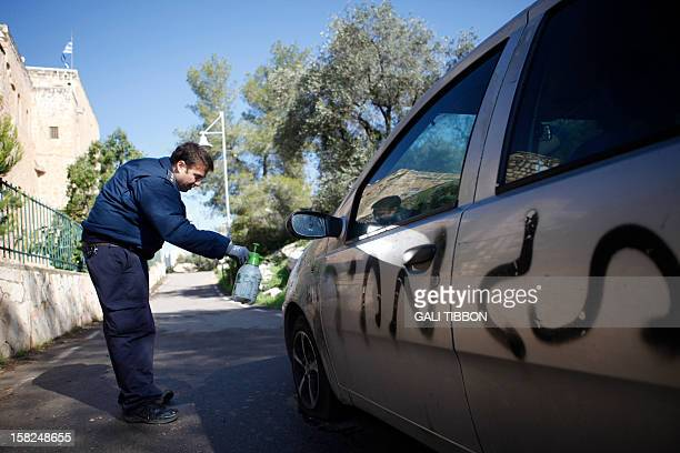 An Israeli forensic policeman examines a car sprayed with antiChristian graffiti reading 'price tag' and slashed tires outside of the Greek Orthodox...