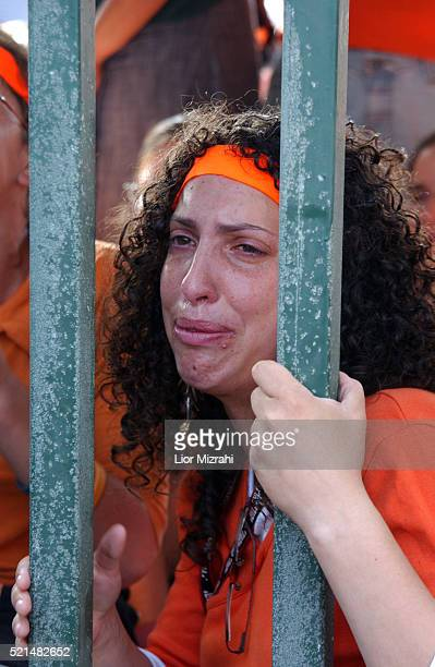 An Israeli girl cries as she holds on to the front gate of the Southern Gaza settlement of Neve Dekalim early 15 August 2005 The army began formal...