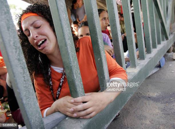 An Israeli girl cries as she holds on to the front gate of the Southern Gaza settlement of Neve Dekalim early 15 August 2005 Israeli soldiers and...