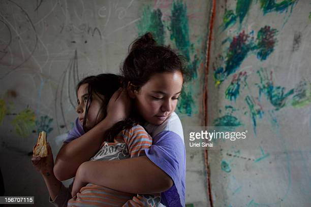 An Israeli girl holds her sister as they take cover in a large concrete pipe used as a bomb shelter during a rocket attack from the Gaza Strip on...