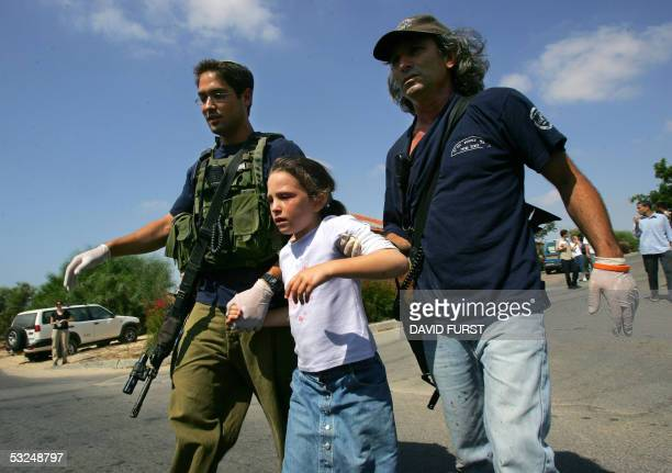 An Israeli girl is escorted by Israeli settler security to a waiting armored van after she was lightly injured by a mortar fired by Palestinian...