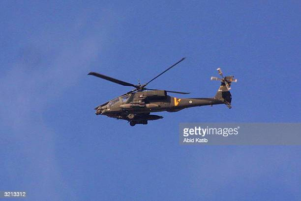 An Israeli helicopter wanders above the Rafah refugee camp during an army operation to uncover tunnels April 3, 2004 in the southern Gaza Strip. The...