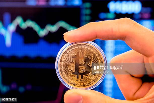 An Israeli holds a visual representation of the digital cryptocurrency Bitcoin at the 'Bitcoin Change' shop in the Israeli city of Tel Aviv on...