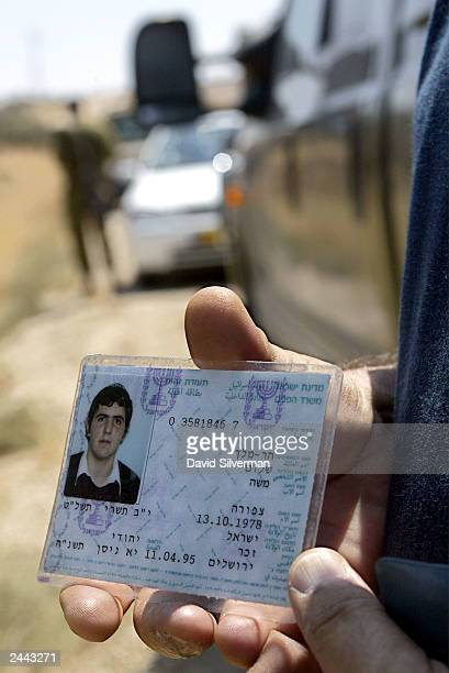 An Israeli holds onto the identity card of slain Jewish settler Shalom Hamelech shortly after was killed August 29 2003 during a Palestinian shooting...