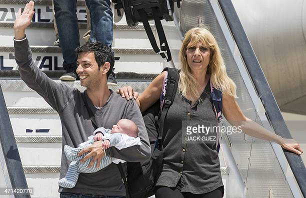 An Israeli homosexual man carries his baby born to a surrogate mother in Nepal as he disembarks a plane at Ben Gurion airport near Tel Aviv on April...