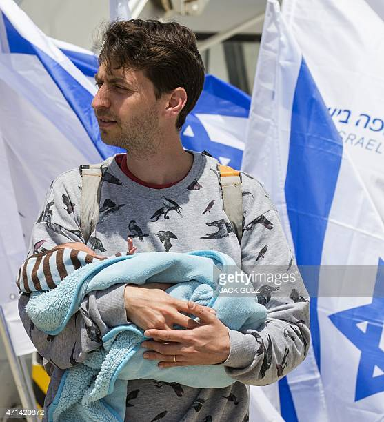 An Israeli homosexual man carrying a baby born to a surrogate mother in Nepal disembarks a plane at Ben Gurion airport near Tel Aviv on April 28...