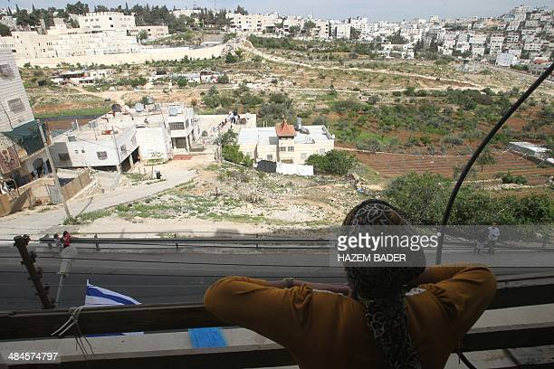 An Israeli Jewish settler looks out from the balcony of her new home down towards Palestinian homes as Jewish settler families move into a fourstorey...