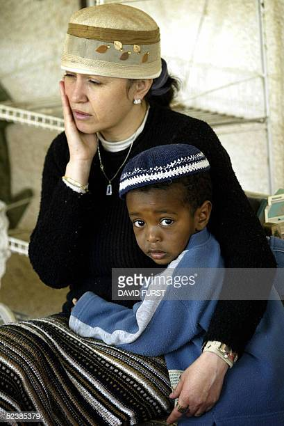 An Israeli kindergarten teacher sits with a young Etheopian settler boy in the Kfar Darom settlement located in the Gush Katif settlement bloc 14...