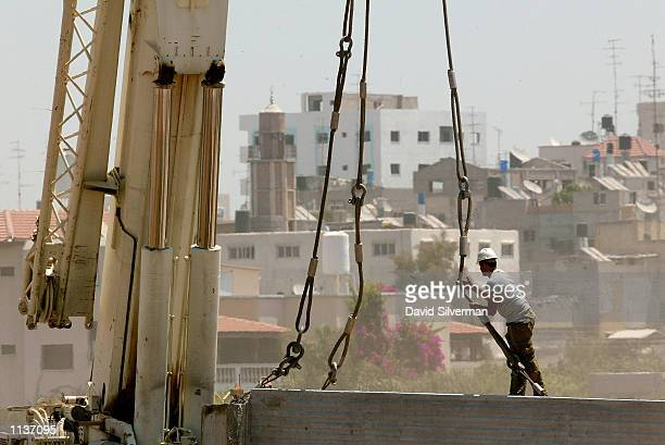 An Israeli laborer works on the 26foot high reinforced concrete wall July 22 2002 being built between the West Bank town of Qalqilya and the Israeli...