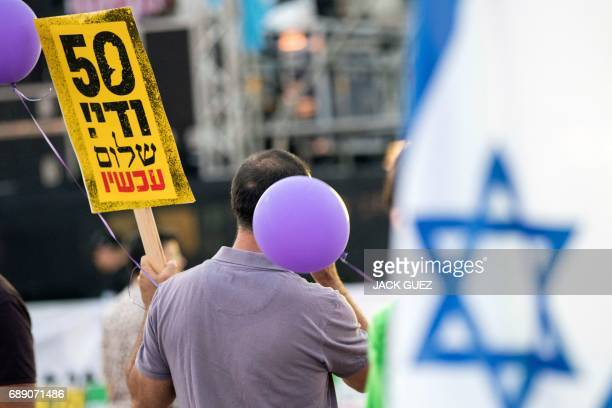 An Israeli leftwing supporter holds a banner reading in Hebrew 50 years is enough during a mass demonstration against 50 years of occupation titled...