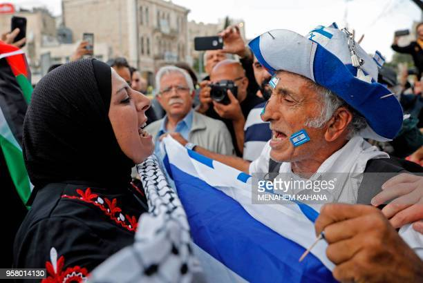 TOPSHOT An Israeli man confronts a Palestinian woman at Damascus gate in Jerusalem on May 13 as Israeli nationalist settlers celebrate the Jerusalem...