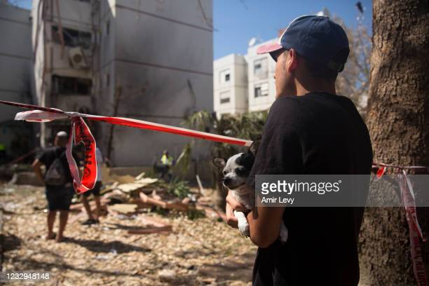 An Israeli man holds his dog at the site of a rocket strike from the Gaza Strip on May 17, 2021 in Ashdod, Israel. In a press conference on Sunday,...