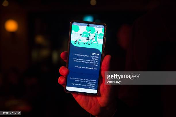 An Israeli man holds his smart phone as he is presenting a 'Covid19' vaccination certificate named 'Green Pass', before entering a bar on March 17,...