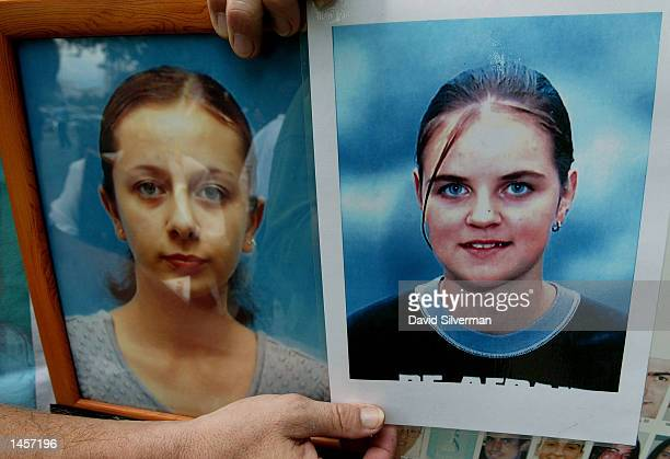An Israeli man holds portraits of teenagers Mariana Medvedenko and Anna Kazachkov who were both killed in the Palestinian suicide bombing at the...