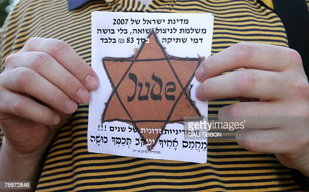An Israeli man holds up a Star of David with 'Jude' German for Jew written on it during a protest of Holocaust survivors and supporters against the...