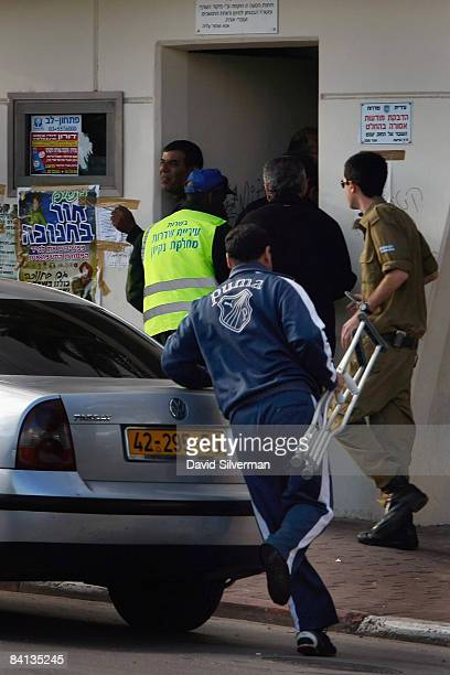 An Israeli man hops towards a bomb shelter holding his crutch as sirens announce an incoming Palestinian Qassam rocket attack on December 29, 2008 in...