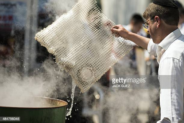 An Israeli man immerses cooking items into boiling water to make them kosher for the Jewish festival of Pessah in Bnei Brak near Tel Aviv on April 14...