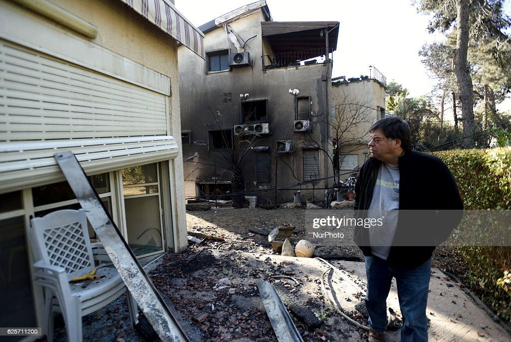 An Israeli man inspects the dammage to a burnt house, hit by a massive forest fire in the Northern city of Haifa, Israel on November 25, 2016. The massive fire in the city of Haifa lead to the evacuation of dozens of thousands of city residents and is part of a lrage wave of forest fires errupted all over Israel during the last days.